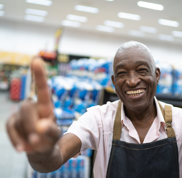 Grocery store employee holding up hand pointing up